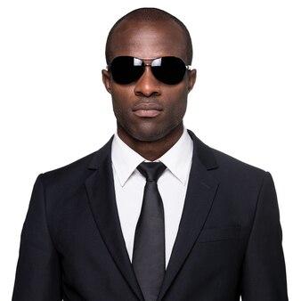 Elegante e fresco. giovane africano serio in abiti da cerimonia e occhiali da sole che guarda l'obbiettivo mentre si sta in piedi isolato su sfondo bianco