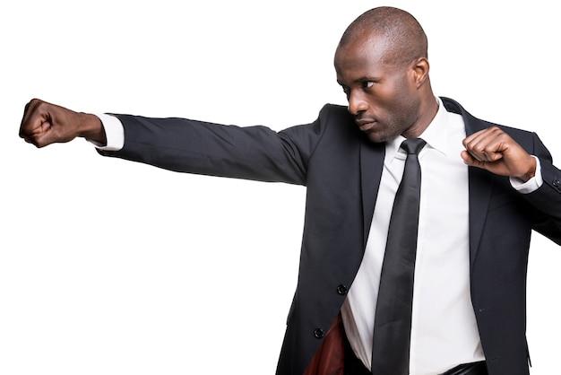 Elegante e fresco. vista laterale di un giovane africano serio in abiti da cerimonia che combatte con qualcuno mentre si trova isolato su sfondo bianco