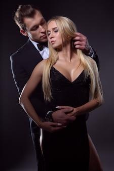 Elegante coppia innamorata in un abbraccio appassionato, foto su sfondo scuro