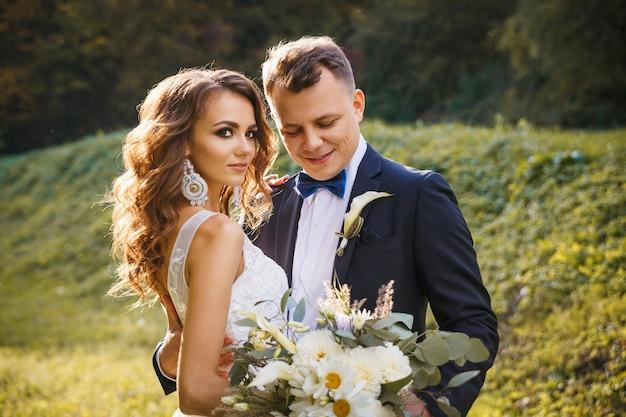 Sposa riccia elegante e sposo alla moda che abbracciano sul prato verde