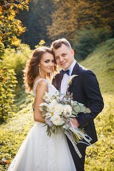 Elegante sposa riccia e sposo alla moda che si abbracciano nel parco