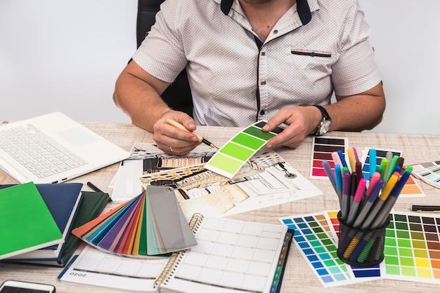 Designer elegante che sceglie il colore per dipingere le pareti della decorazione dell'appartamento dei tuoi sogni