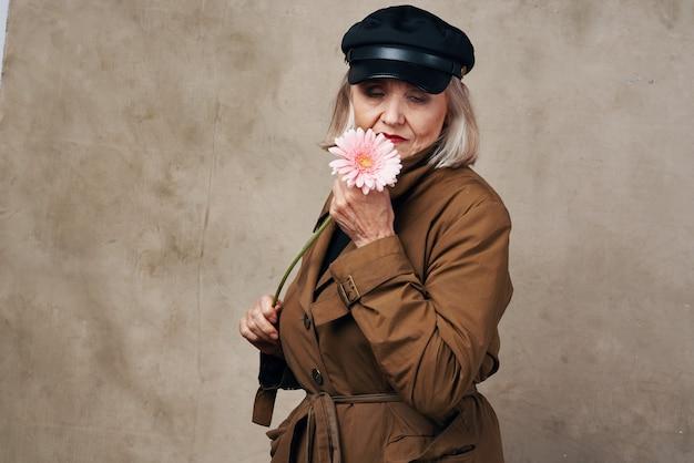 Elegante donna anziana in cappotto che tiene un fiore alla moda