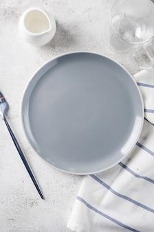 Elegante piatto vuoto, posate, tazza di caffè per la colazione mattutina, sfondo tavolo luminoso, vista dall'alto. regolazione del posto del tavolo della colazione in colore bianco.