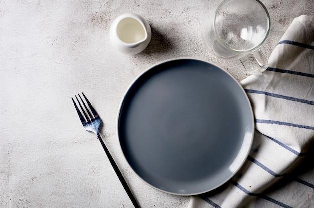 Elegante piatto vuoto, posate, tazza di caffè per mangiare al mattino, sfondo tavolo luminoso, vista dall'alto.