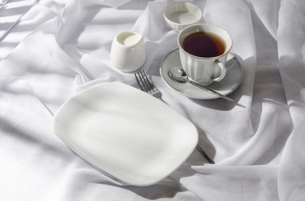 Elegante piatto vuoto, posate, tazza di caffè al mattino soleggiato, sfondo bianco pulito della tovaglia, vista dall'alto. regolazione del posto del tavolo della colazione in colore bianco.