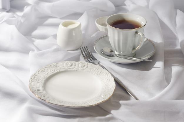 Piatto vuoto elegante, coltelleria, tazza di caffè la mattina soleggiata, fondo bianco pulito della tovaglia,