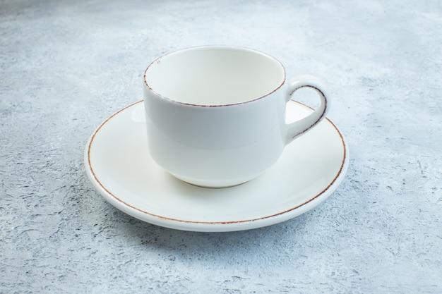 Elegante tazza bianca vuota e salsa su superficie grigia isolata con superficie angosciata