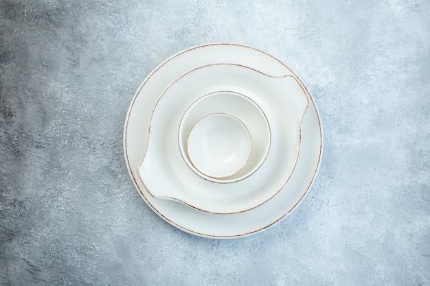 Elegante set bianco vuoto per cena su superficie grigia isolata con spazio libero
