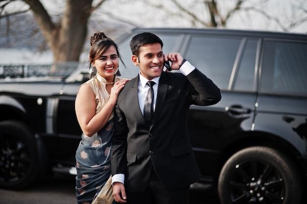 Coppia di amici indiani eleganti e alla moda di donna in sari e uomo in abito posato contro ricca auto suv nera. guy parla al cellulare.