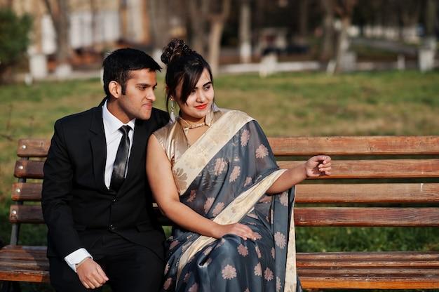 Coppia di amici indiani eleganti e alla moda di donna in sari e uomo in tuta seduto sulla panchina.