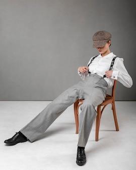 Elegante modello femminile in posa su una sedia in elegante camicia bianca e bretelle. nuovo concetto di femminilità