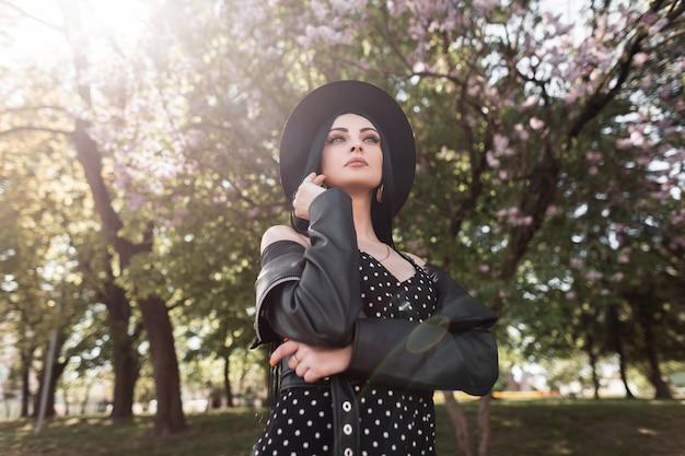 Elegante modello di giovane donna fine in cappello nero alla moda in elegante abito estivo in giacca di pelle vintage gode di relax nel parco fiorito contro i raggi di sole. la splendida ragazza bruna riposa sul sole.
