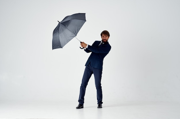 Elegante gentiluomo con ombrello scuro su sfondo chiaro e abito classico