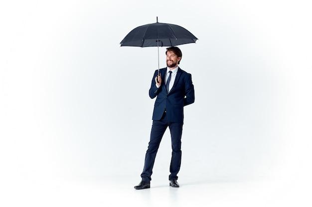Gentiluomo elegante con un ombrello scuro su sfondo chiaro e un abito classico