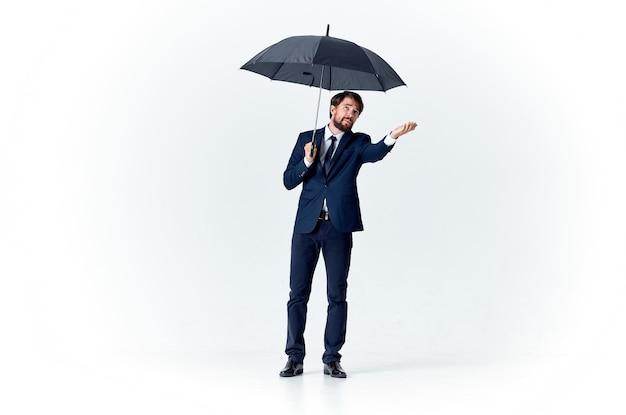 Gentiluomo elegante con un ombrello scuro su uno spazio luminoso e un abito classico