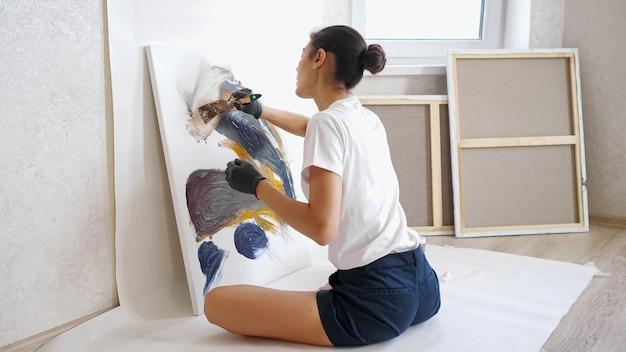 Elegante ragazza artista si siede in posa yoga sul pavimento di legno e disegna con le mani in guanti neri e spazzola a casa sotto la brillante luce del sole estivo