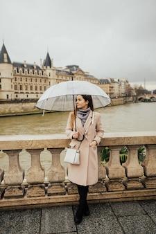Turista della ragazza elegante in piedi su un ponte sulla senna a parigi.