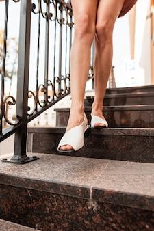 Ragazza elegante con belle gambe in sandali di cuoio estivi alla moda scende le scale di pietra in città. avvicinamento.