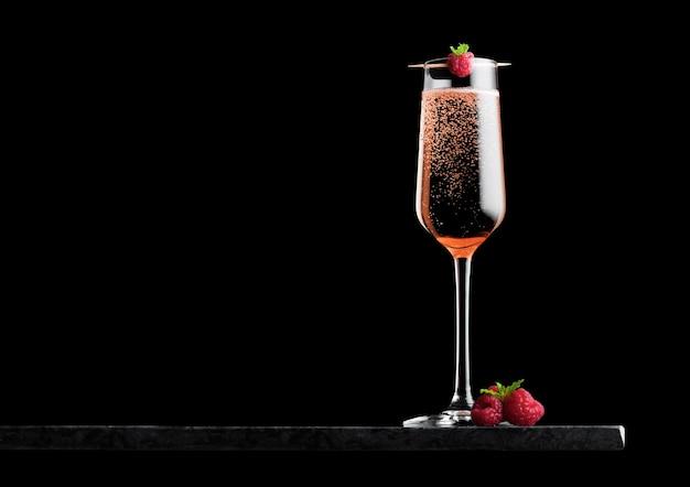 Elegante bicchiere di champagne rosa rosa con lampone