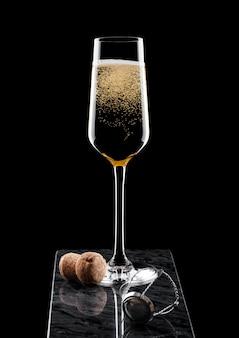 Elegante bicchiere di champagne giallo con sughero e gabbia metallica sul bordo di marmo nero sul nero.