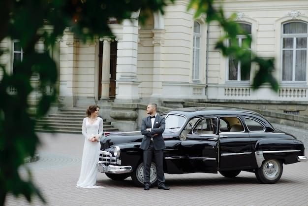 Sposa splendida elegante e sposo bello che si abbracciano in elegante automobile nera alla luce.
