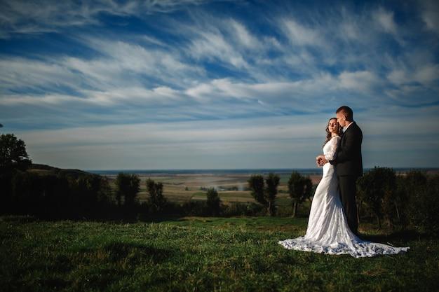 Lo sposo elegante abbraccia una bellissima sposa bruna su uno sfondo di natura e cielo blu