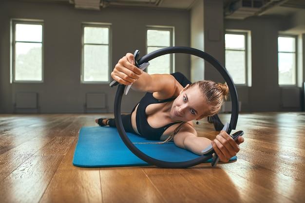 Le mani invertite dell'insegnante di ginnastica elegante sostengono il corpo sul pavimento e le gambe sull'anello di pilates con il corpo elasticizzato sviluppano la morbidezza nello studio del fondo grigio della parete