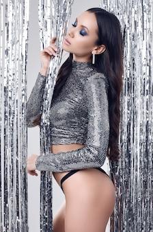 Elegante donna ispanica bruna con un corpo perfetto in lussuoso top con paillettes