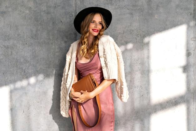 Elegante ritratto al coperto di bella donna glamour in posa vicino al muro grigio in una giornata di sole, indossando un abito di seta, un caldo cardigan lavorato a maglia e un cappello nero