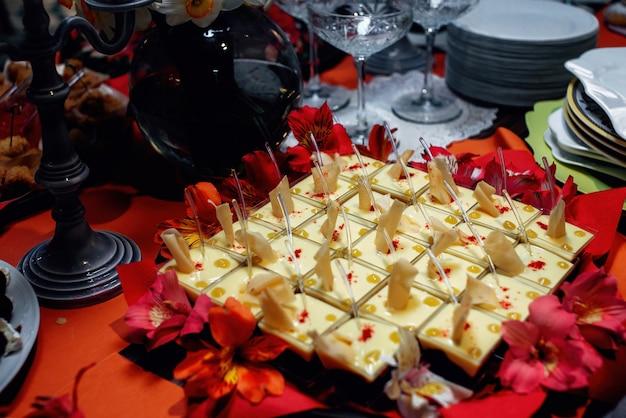 Un'elegante merenda con gelatina e mousse decorata con fiori panna cotta in ciotoline quadrate