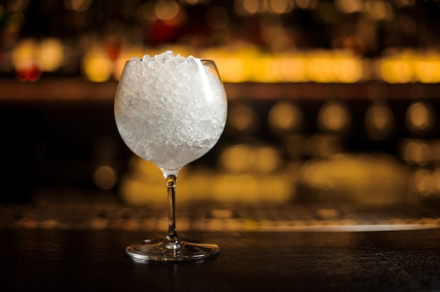 Elegante bicchiere da cocktail rotondo grande riempito con molto ghiaccio sul bancone del bar in controluce
