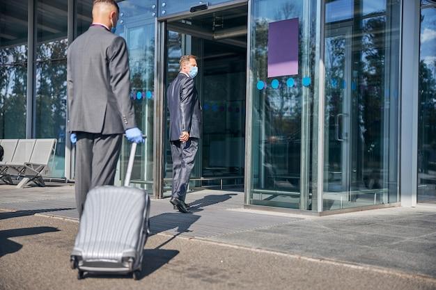 Il maschio elegante sta andando in viaggio e l'autista sta portando i suoi bagagli all'ingresso del terminal mentre indossa maschere sterili