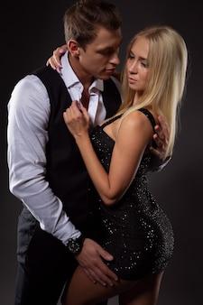 Un uomo elegante abbraccia dolcemente un'affascinante bionda in un corto abito nero, foto su uno sfondo scuro
