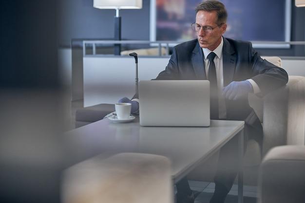L'uomo elegante con gli occhiali e i guanti in lattice sta lavorando al computer portatile con una tazza di caffè prima del volo durante la quarantena
