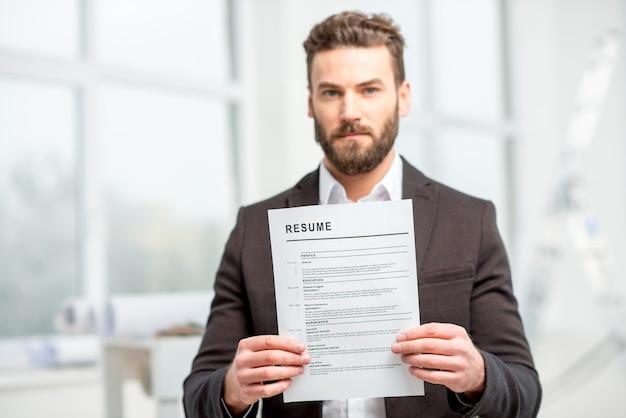 Uomo elegante nel vestito che tiene il curriculum per l'assunzione di lavoro negli interni luminosi. immagine focalizzata in primo piano sulla carta