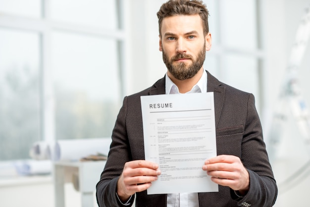Elegante uomo vestito che tiene in mano un curriculum per l'assunzione di lavoro negli interni luminosi
