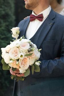 Un uomo elegante in abito a tre pezzi con un papillon bordeaux tiene in mano un bouquet rotondo con eustoma e rose