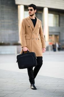Uomo elegante che cammina all'aperto tenendo una valigetta