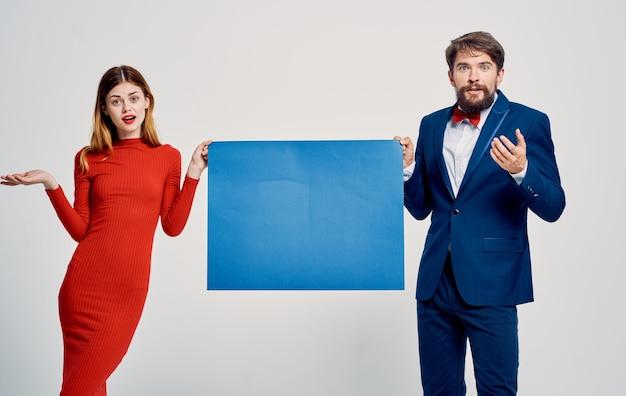 Uomo e donna eleganti che tengono il manifesto del modello a disposizione pubblicità