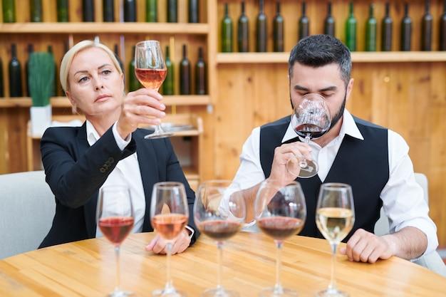 Elegante uomo e donna seduti a tavola in cantina mentre esaminano il colore, il gusto e l'odore di nuovi tipi di vino