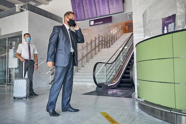 Elegante uomo maturo in maschera sta effettuando una chiamata mentre aspetta la partenza con l'assistente e il trasporto dei bagagli