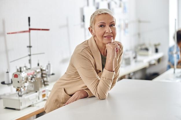 Elegante donna matura in giacca beige si appoggia sul tavolo da taglio bianco nel laboratorio di cucito