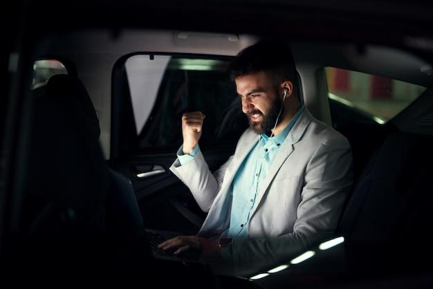 Elegante uomo d'affari moderno con laptop sul sedile posteriore per celebrare il successo del lavoro.