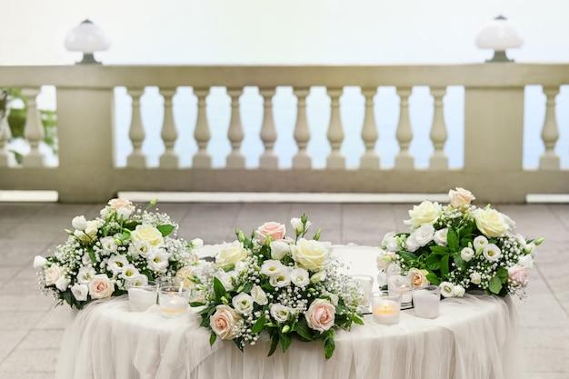 Elegante tavolo da matrimonio all'aperto con tre mazzi di fiori rosa e bianchi e candele su un patio all'aperto con balaustra