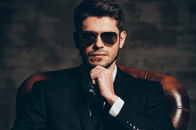 Elegante e perfetto. ritratto di giovane uomo bello in vestito che tiene la mano sul mento e guardando la fotocamera mentre è seduto in poltrona di pelle su sfondo grigio scuro