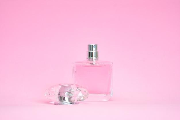 Elegante bottiglia di profumo con coperchio aperto su sfondo rosa pastello