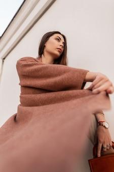 Elegante ritratto bella giovane donna in cappotto alla moda con borsa in pelle marrone vicino al muro bianco vintage sulla strada. modello di moda bella ragazza. signora di bellezza in capispalla elegante primavera all'aperto.