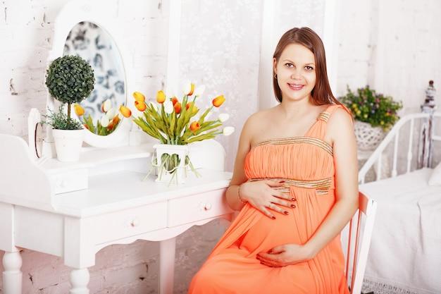 Elegante donna incinta che abbraccia la sua pancia