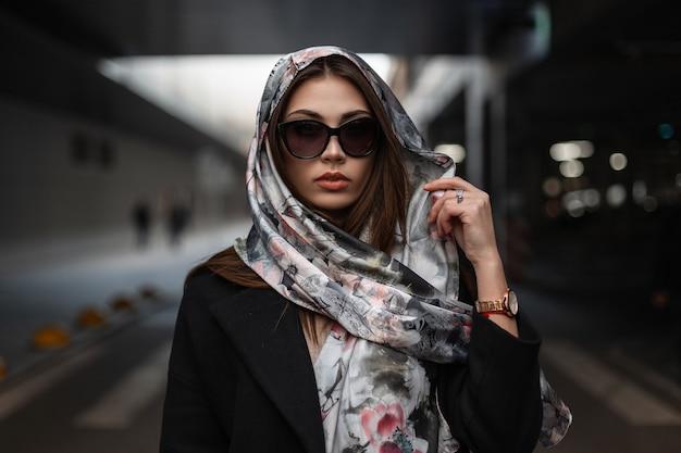 Elegante bella giovane donna in abiti alla moda in posa all'aperto. ritratto bella ragazza in occhiali da sole scuri alla moda in un cappotto con una lussuosa sciarpa di seta sulla testa in città. signora degli affari urbani.